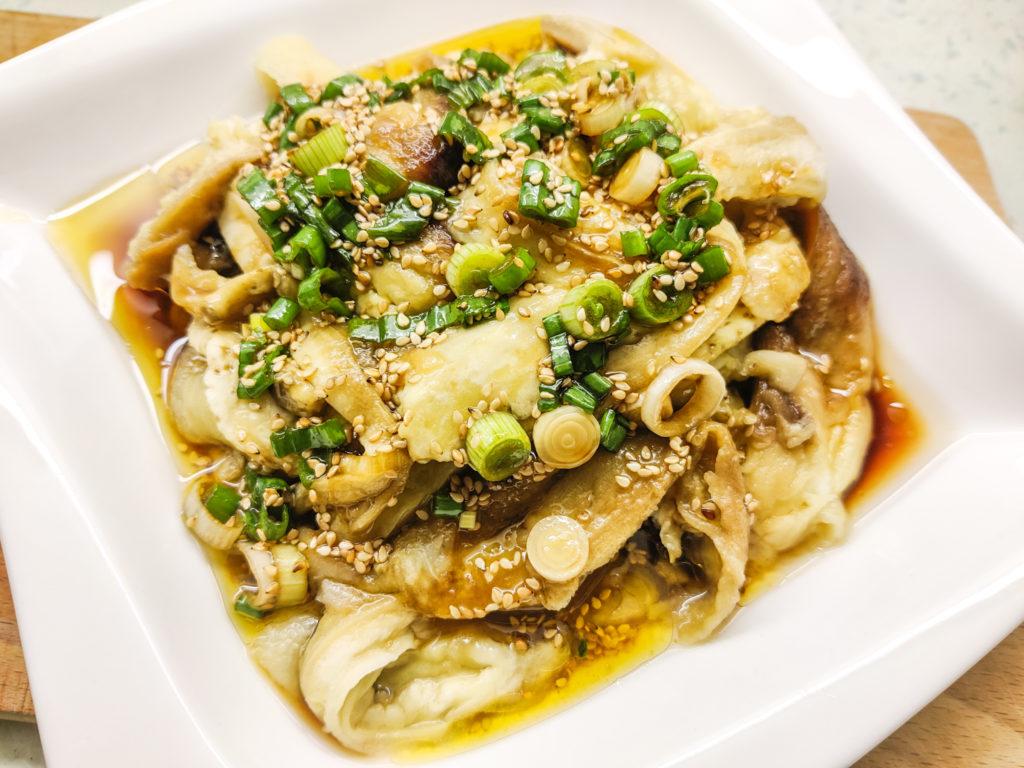 Čínský dušený lilek se sojovou omáčkou a sezamovým olejem servírovaný na talíří